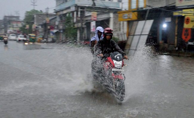A two wheeler moves through a waterlogged street after heavy downpour in Agartala...