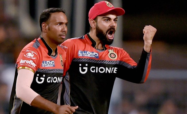 Virat Kohli celebrates with bowler S Badree after dismissal of Robin Uthappa
