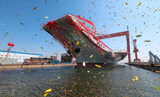 A newly-built aircraft carrier is transferred from dry dock into the water at a launch ceremony...
