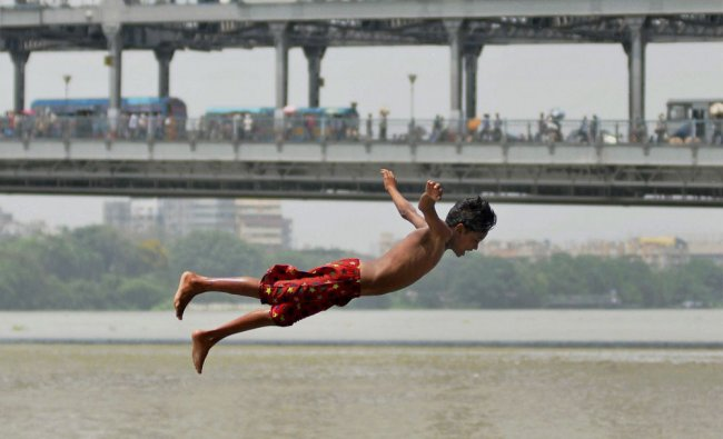 A boy jumps into the river Ganga to beat the heat in Kolkata on Wednesday...