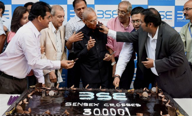 A cake weighing 30 kg is cut as part of celebrations outside BSE as Sensex ended above the...