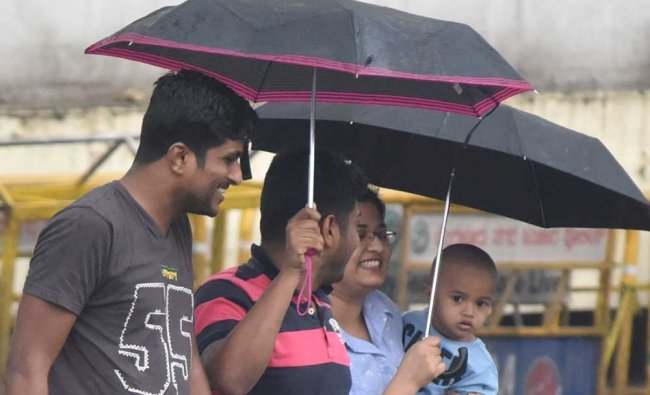 People use umbrella to protect from rain at at MG Road and Kasturba Road junction in Bengaluru...