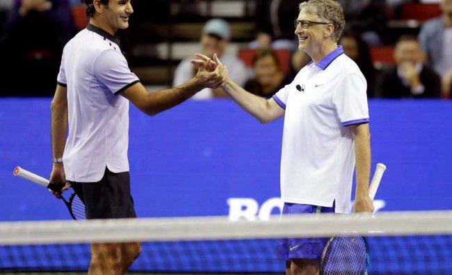 Roger Federer, of Switzerland, left, and Microsoft founder Bill Gates, right, celebrate...