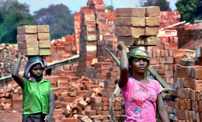 Laborers carrying bricks at a brick factory on the eve of International labour day on the outskirts.