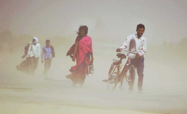 People walk through a dust storm in Allahabad on Monday....