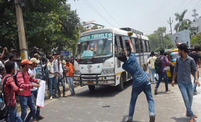 Students damaging a bus during their protest against...