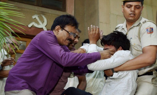 Police take away a Hindu Sena activist who was trying to disrupt CPI(M) general secretary...