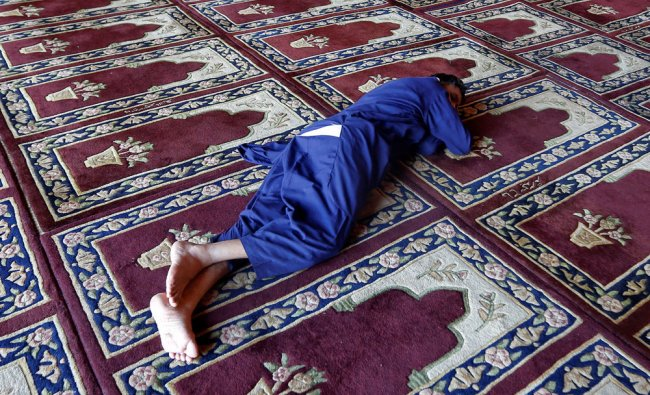 A man takes a nap after offering prayers inside Jamia Masjid or Grand Mosque...