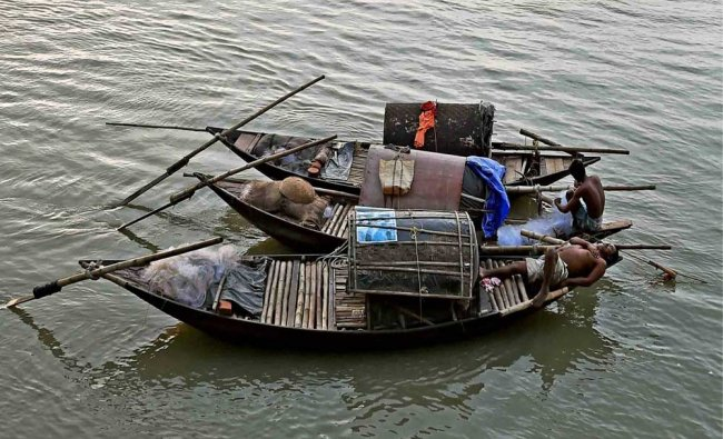 A fisherman takes nap on a boat while another busy with nets...