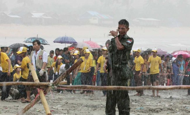A soldier braves the monsoon rain as bodies recovered by fishing vessels...
