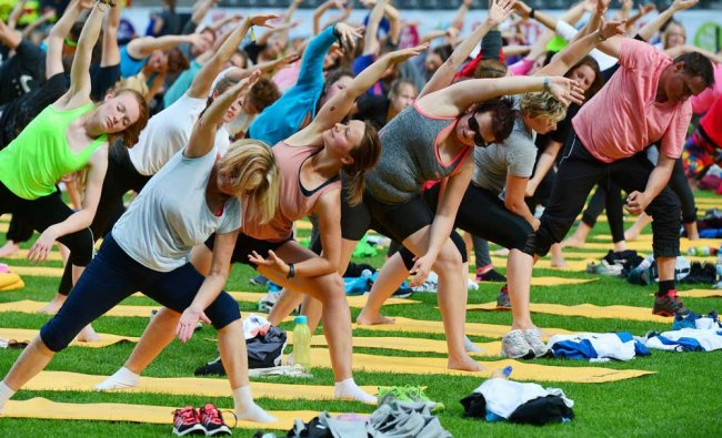 Hundreds of participants take part in a yoga and dance-centred fitness session...