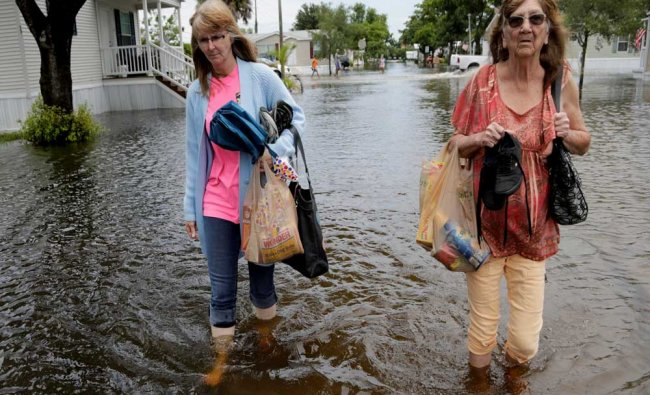 Adrienne Brooks, left, walks with her mother Joan Jones, right, through flooded streets...