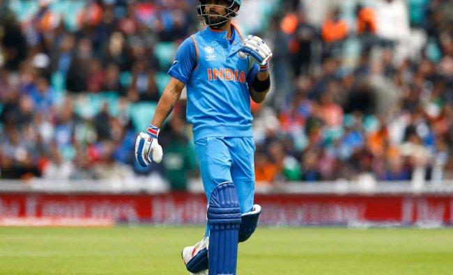 India\'s Virat Kohli walks off dejected after losing his...