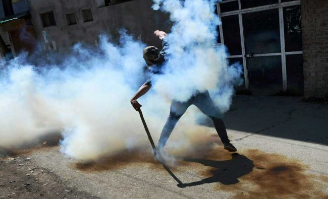 A protester throws a teargas shell back to the police during a clash in Srinagar on Friday...