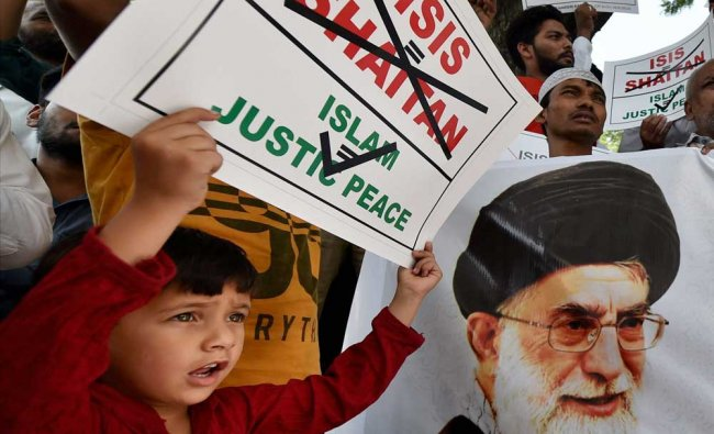A child displays a placard as Muslims protest in New Delhi on Friday against ...