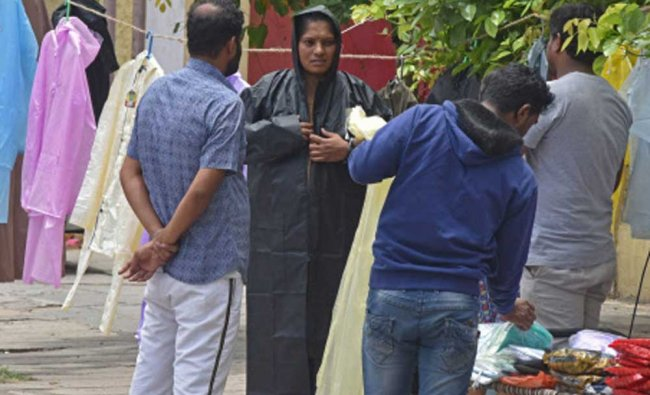 people purchasing raincoat for rainy session at Bull Temple road in Bengaluru on Saturday.
