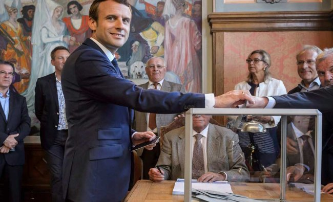 French President Emmanuel Macron casts his ballot in the first round of the two-stage legislative..