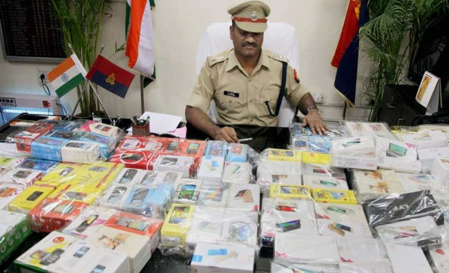 Police showing 130 mobile phones recovered from a gang of six criminals during a press conference..