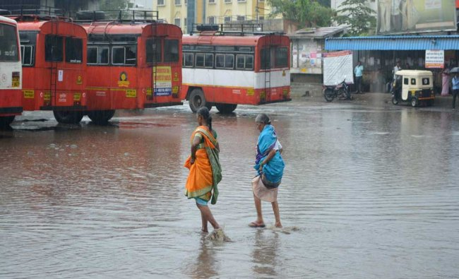 Women make their way through flooded bus stand after heavy rainfall in Karad, Maharashtra...