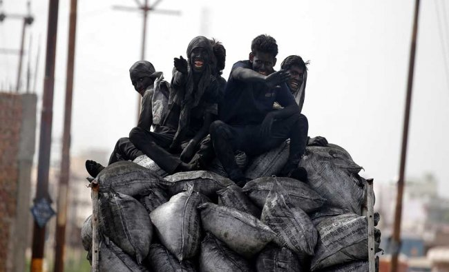 Coal workers travel on the back of their lorry in Barsana, India...