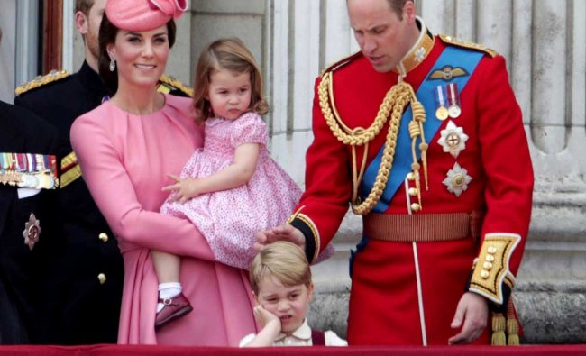 Kate, The Duchess of Cambridge, holds Princess Charlotte...