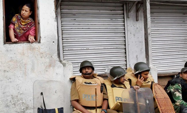 Security personnel guard sit as woman looks out of window in Darjeeling on Sunday.