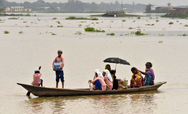 School children and women are transported in a boat to a safer place in a flooded wetland...