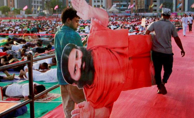 Volunteers carry cutout of Yoga Guru Baba Ramdev ahead of International Yoga day in Ahmedabad...