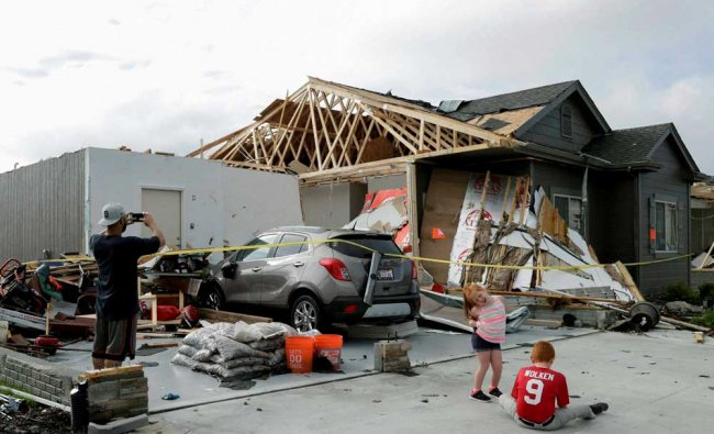 A neighbor and grand children of absent homeowners are seen in front of a weather-damaged home...