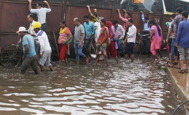 People crossing a flooded road after heavy rains in Gurugram on Monday...