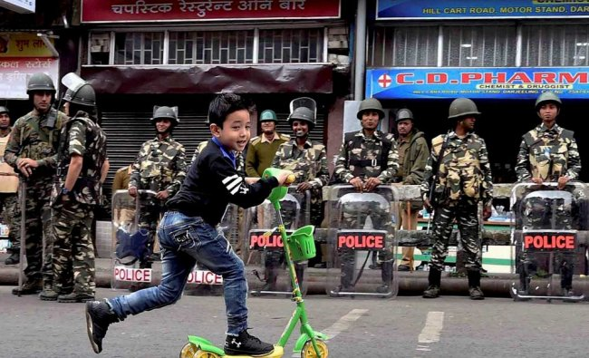 A small boy plays with a scooter at a road as security forces personnel guard during Gorkha Janamukt