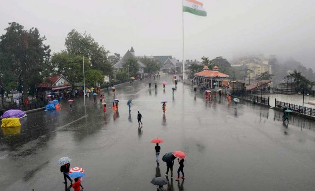 People enjoying the rains at the historic Ridge in Shimla on Wednesday.
