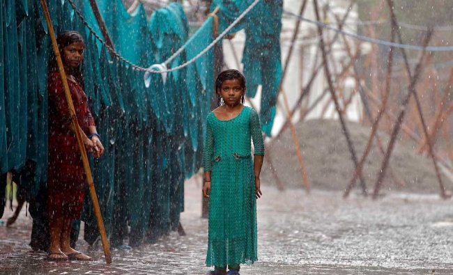 Girls stand in monsoon rains beside an open laundry in New Delhi...