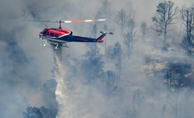 A helicopter drops water as U.S. Forest Service firefighters and several other departments battle...