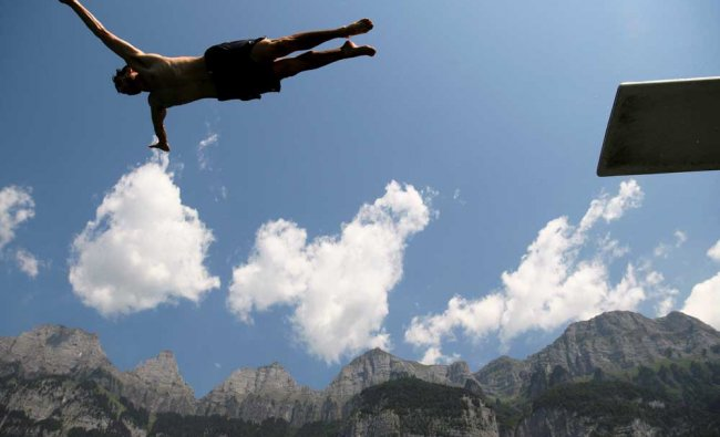 A man jumps into Lake Walensee, with the Churfristen mountain range in the background...