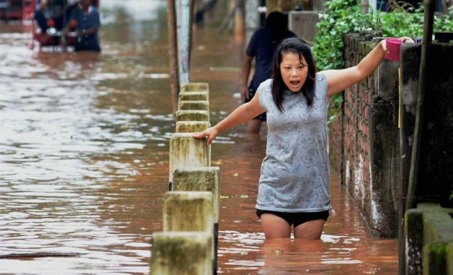 A woman gingerly makes her way through a flooded road in Guwahati after heavy rains...