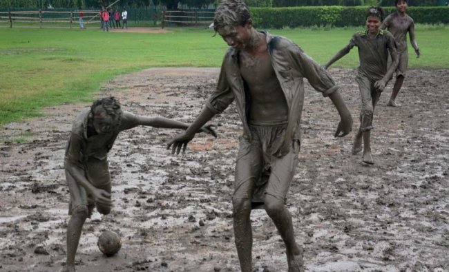 Children play football in mud after rainfall in Kolkata on Friday. PTI