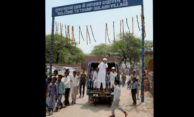 Children are seen near the entrance gate of Maroda Village which was renamed as \'Trump Village\'...