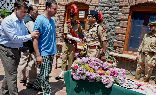 A police officer offers supports to the son of slain DSP Mohammed Ayub Pandit to pay respects to...