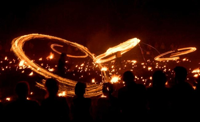 People move around themselves fire\'s torch during the San Juan night in the small Pyrenees...