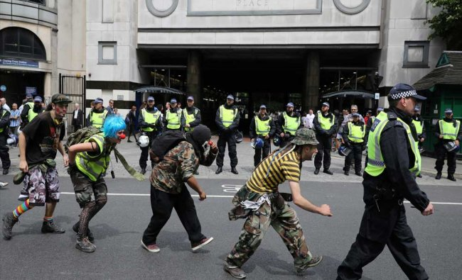 Demonstrators walk behind a police officer during an anti-fascist march, in central, London...