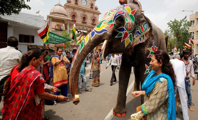 Hindu devotees give money to a decorated elephant outside the Jagannath temple on the eve of the...