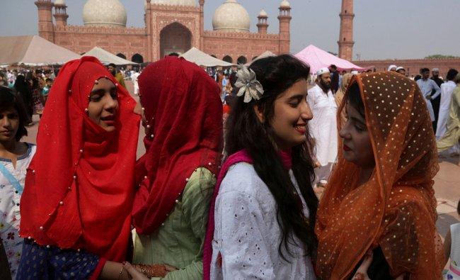 Pakistani women greet each others after the Eid al-Fitr prayers...
