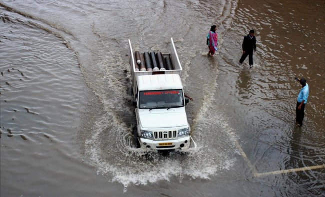 A vehicle wades through a waterlogged road...
