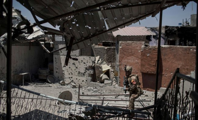 An Iraqi special forces soldier walks by a damaged house during fighting...