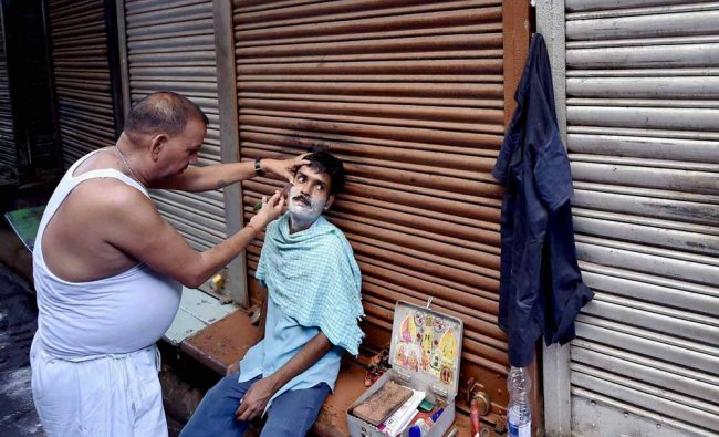 A barber attends a customer at the closed Burrabazar during a bandh against GST...