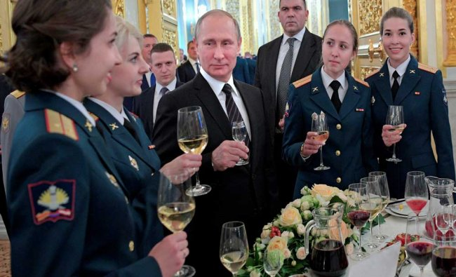 Russian President Vladimir Putin, center, toasts at a meeting with graduates of military...