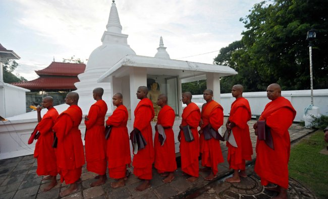A group of Buddhist monks stand in a line during a religious ceremony at a temple in Colombo...