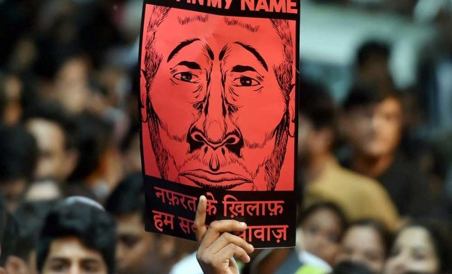 A participant shows a placard during a silent protest \'Not in My Name\' against the targeted...