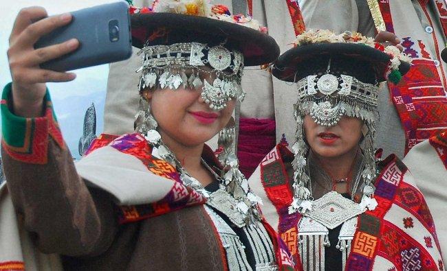 Artists, in traditional Kinnauri attire, take a selfie break during a function...